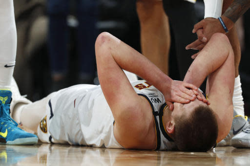 Denver Nuggets center Nikola Jokic holds his face after it was hit while he and Los Angeles Lakers forward LeBron James vied for a rebound in overtime of an NBA basketball game Wednesday, Feb. 12, 2020, in Denver. The Lakers won 120-116. (AP Photo/David Zalubowski)