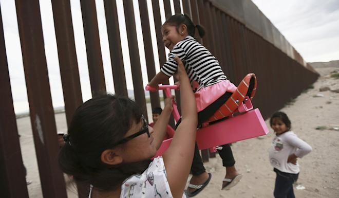 A woman in Mexico helps girls play on a seesaw installed at the border fence between Mexico and the US on Sunday. Photo: AP