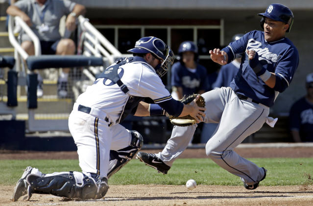 Milwaukee Brewers catcher Jonathan Lucroy, left, cannot handle a throw as San Diego Padres' Everth Cabrera scores from first on a single by Alexi Amarista during the second inning an exhibition spring training baseball game on Friday, March 7, 2014, in Phoenix. (AP Photo/Morry Gash)