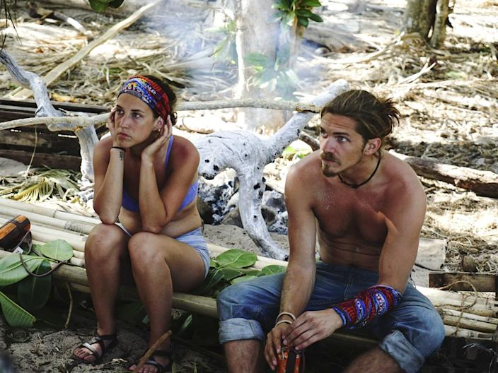"""Ciera Eastin and Malcolm Freberg sitting on a log with some smoke in the background on """"Survivor"""""""