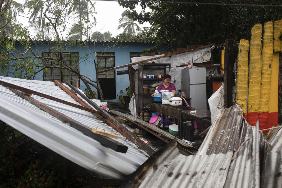 A woman begins clearing debris from her kitchen after a part of her home was damaged by winds brought on by Hurricane Grace, in Tecolutla, Veracruz State, Mexico, Saturday, Aug. 21, 2021. Grace hit Mexico's Gulf shore as a major Category 3 storm before weakening on Saturday, drenching coastal and inland areas in its second landfall in the country in two days. (AP Photo/Felix Marquez)
