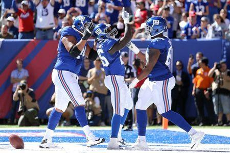Sep 25, 2016; East Rutherford, NJ, USA; New York Giants running back Orleans Darkwa (26) celebrates with offensive tackle Ereck Flowers (74) and guard Bobby Hart (68) after scoring a touchdown against the Washington Redskins during the second quarter at MetLife Stadium. Mandatory Credit: Brad Penner-USA TODAY Sports