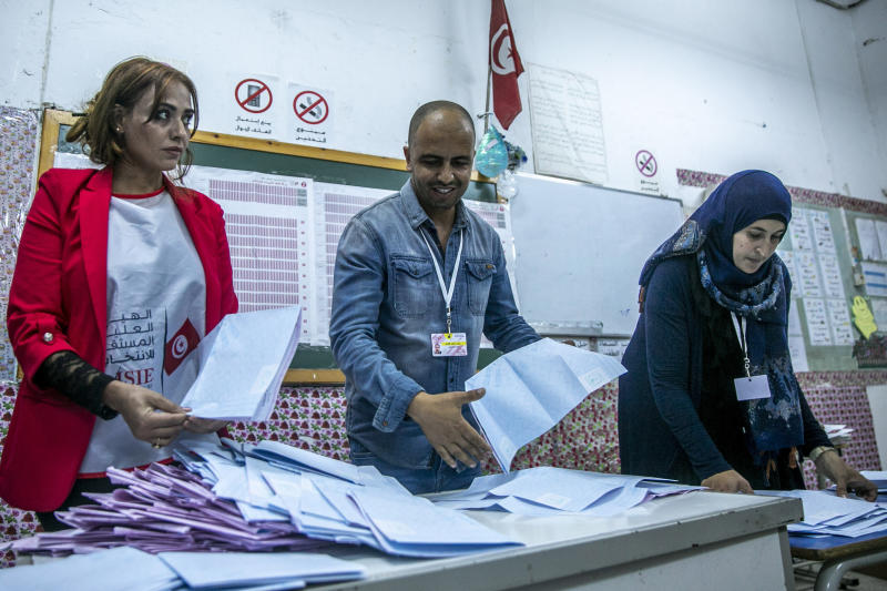 Election officials start counting marked ballots after polling stations closed during a parliamentary election in Tunis, Tunisia, Sunday, Oct. 6, 2019. Tunisians were electing a new parliament Sunday amid a tumultuous political season, with a moderate Islamist party and a jailed tycoon's populist movement vying to come out on top of a crowded field. (AP Photo/Riadh Dridi)