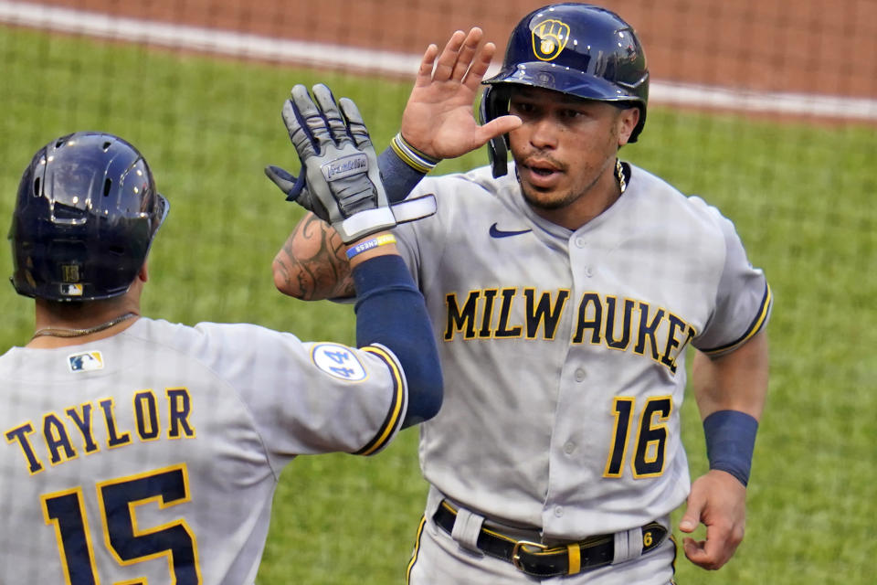 Milwaukee Brewers' Kolten Wong (16) returns to the dugout after scoring from second on a single by Avisail Garcia off Pittsburgh Pirates starting pitcher Max Kranick during the first inning of a baseball game in Pittsburgh, Wednesday, July 28, 2021. (AP Photo/Gene J. Puskar)