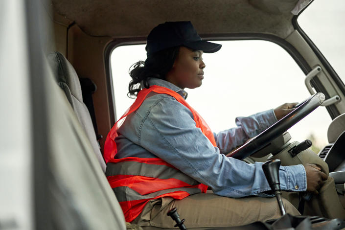 Side view of mid 20s woman in casual clothing, reflective vest, and cap sitting in driver's seat of vehicle cab, ready to start road trip.
