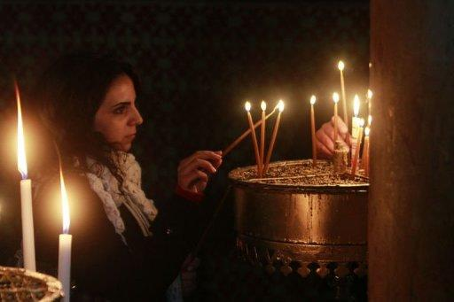 A woman lights a candle at the Church of the Nativity, in Bethlehem December 21, 2012
