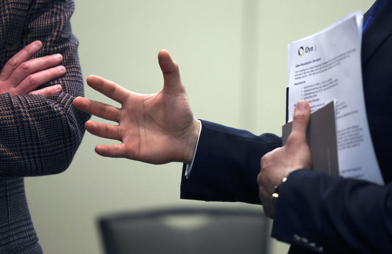 In this Monday, Feb. 25, 2013, photo, Sayed Mouawad, right, of Providence, R.I., gestures while speaking to a company representative during a job fair in Boston. The Labor Department is scheduled to release the jobs report at 8:30 a.m. EST Friday March 8, 2013. (AP Photo/Michael Dwyer)