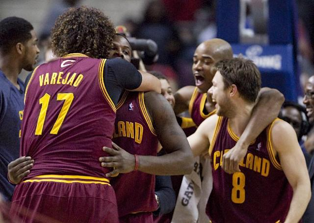 FILE - In this March 26, 2014 file photo, Cleveland Cavaliers guard Dion Waiters, second from left, is hugged by teammate Anderson Varejao (17) after sinking a two-point basket to defeat the Detroit Pistons in an NBA basketball game in Auburn Hills, Mich. With seven games left, and a favorable schedule the rest of the way, the Cavaliers are in the mix to make the playoffs for the first time since 2010, when LeBron James was in his final days wearing wine and gold. (AP Photo/Duane Burleson, File)