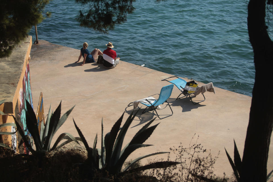 Sunbathers enjoy the beach in Palma de Mallorca, Spain, Sunday, July 26, 2020. Britain has put Spain back on its unsafe list and announced Saturday that travelers arriving in the U.K. from Spain must now quarantine for 14 days. The move by the UK taken without forewarning has caught travelers off guard. (AP Photo/Joan Mateu)