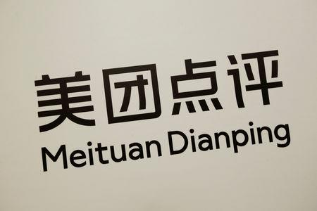 FILE PHOTO: A company logo of China's Meituan Dianping, an online food delivery-to-ticketing services platform, is displayed at a news conference on its IPO in Hong Kong, China September 6, 2018. REUTERS/Bobby Yip