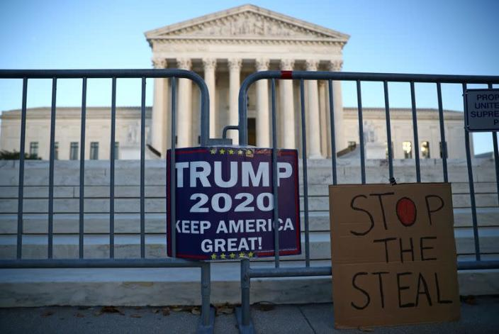 FILE PHOTO: Signs by supporters of U.S. President Donald Trump hang outside the U.S. Supreme Court building in Washington