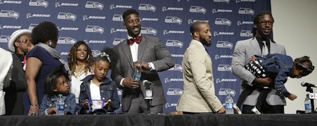 Seattle Seahawks' Marcus Trufant, center, smiles as he stands with family members following a news conference announcing his retirement from football after signing with the team a day earlier, Thursday, April 24, 2014, in Renton, Wash. Trufant started 125 games in a Seattle career that lasted from 2003 to 2012. The cornerback was a first-round pick in 2003 out of Washington State and immediately moved into the starting lineup, playing a key role on the 2005 team that advanced to the franchise's first Super Bowl. (AP Photo/Elaine Thompson)