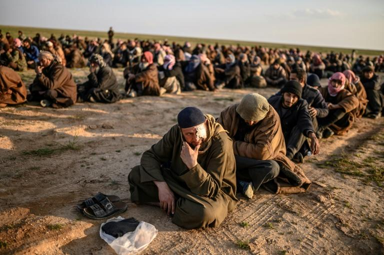 Suspected Islamic State group fighters wait to be searched after leaving the jihadists' last holdout in eastern Syria