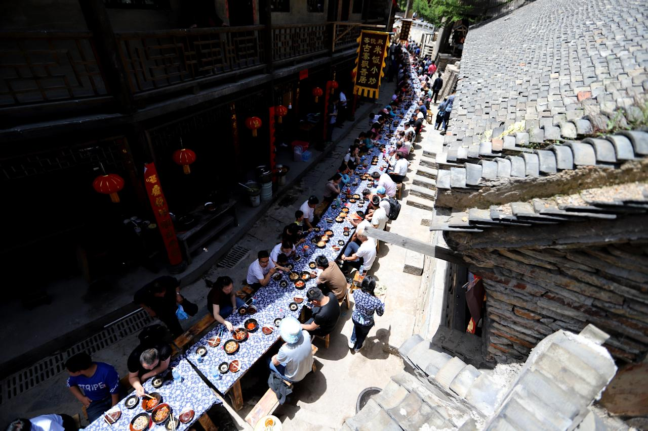 <p>Villagers and tourists enjoy food for free at a long-table banquet during a tourism festival at Baodu Village scenic area on May 13, 2018 in Luoyang, Henan Province of China. Tables were laid end to end along the street and about 200 diners sitting on either side of the 'long table' were treated to a feast. (Photo from VCG/VCG via Getty Images) </p>