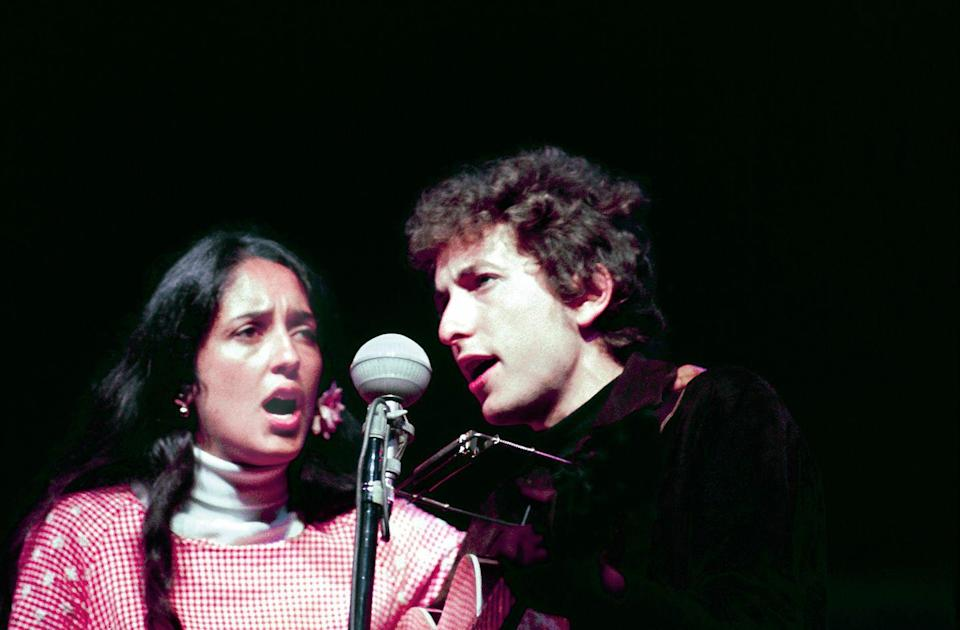<p>Joan Baez and Bob Dylan performing live onstage at the Newport Folk Festival in 1964.</p>