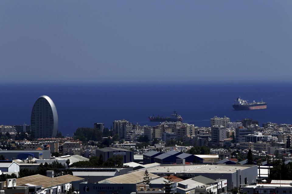 """FILE - This Friday, July 6, 2018 file photo, shows the Oval building, left, one of a number of new high-rises transforming the skyline view, of the southern coastal city of Limassol in the eastern Mediterranean island of Cyprus. Cyprus government spokesman Kyriakos Koushos said on Tuesday, Oct. 13, 2020, that the Cabinet accepted a recommendation by the minsters of the interior and finance to cancel altogether the """"golden passport"""" program that has netted billions of euros over several years. Koushos said the decision was based on the Cyprus Investment Program's """"long-standing weaknesses, but also the abuse"""" of its provisions. (AP Photo/Petros Karadjias, File)"""