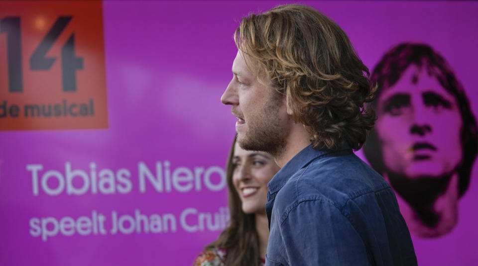 """Tobias Nierop, who plays soccer legend Johan Cruyff, and Myrthe Burger, rear, who plays his wife Danny, are seen during a presentation of """"14 The Musical"""" in Leusden, Netherlands, Friday, June 11, 2021. On the opening day of the pandemic-delayed European 2020 Soccer Championship, the cast and crew of """"14 The Musical"""", referring to Cruyff's shirt number, raised the curtain on the new musical eulogizing the country's most famous footballing son, Johan Cruyff. (AP Photo/Peter Dejong)"""