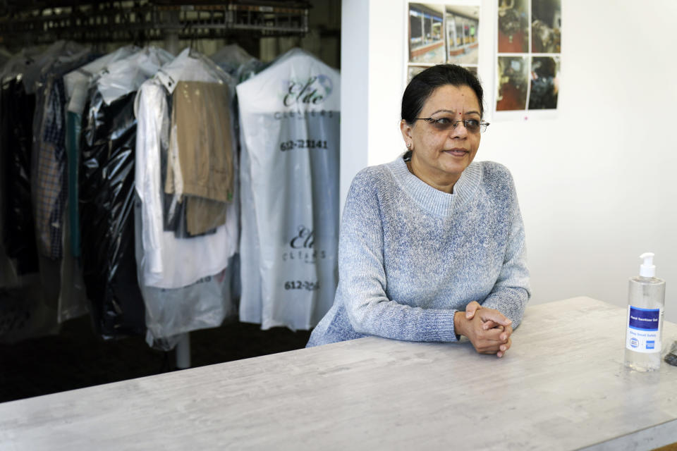 Pinky Patel, who immigrated from India and whose family owns Elite Cleaners, poses March 25, 2021, at her business down the street from the destroyed 3rd Precinct police station in Minneapolis. Looters stripped the shop of clothing and set fire to the equipment following the death of George Floyd at the hands of police last May. The Lake Street Council estimates that small businesses sustained about $250 million in uninsured damage along the corridor, from broken windows to large buildings that had to be torn down. (AP Photo/Jim Mone)
