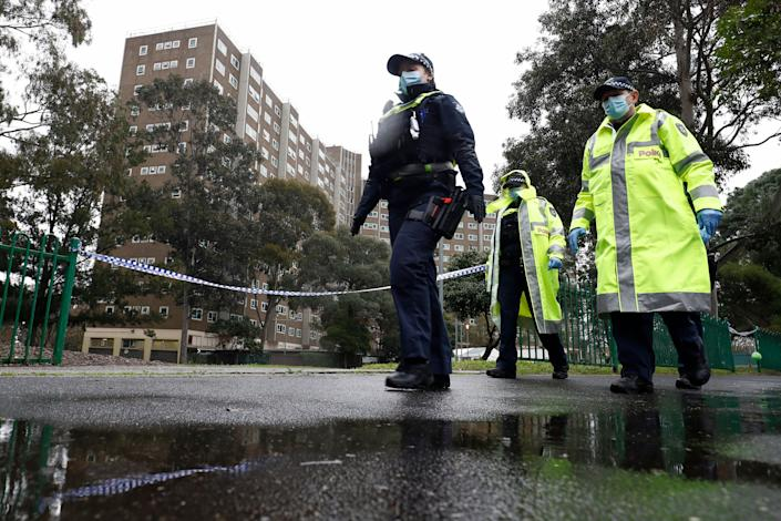 """Members of the Victoria police patrol outside a public housing tower that was placed under """"hard lockdown"""" in Melbourne on July 11, 2020. (Photo: Darrian Traynor via Getty Images)"""