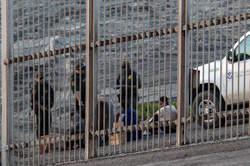 Central American migrants are taken into custody by US Border Patrol officers after crossing the Mexico-US border fence near San Diego, California (AFP Photo/Guillermo Arias)
