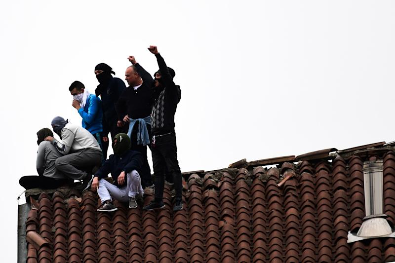 Inmates stage a protest on a rooftop of a wing at the San Vittore prison in Milan on March 9, 2020, in one of Italy's quarantine red zones. - Inmates in four Italian prisons have revolted over new rules introduced to contain the coronavirus outbreak, leaving one prisoner dead and others injured, a prison rights group said on March 8. Prisoners at jails in Naples Poggioreale in the south, Modena in the north, Frosinone in central Italy and at Alexandria in the northwest had all revolted over measures including a ban on family visits, unions said. (Photo by Miguel MEDINA / AFP) (Photo by MIGUEL MEDINA/AFP via Getty Images)