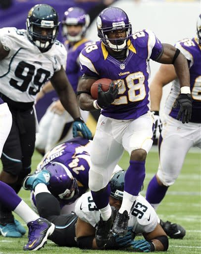 Minnesota Vikings running back Adrian Peterson rushes away from Jacksonville Jaguars defensive tackle C.J. Mosley (99) and defensive end Tyson Alualu (93) during overtime of an NFL football game, Sunday, Sept. 9, 2012, in Minneapolis. The Vikings won 26-23. (AP Photo/Genevieve Ross)