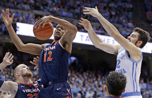 Virginia's De'Andre Hunter (12) and North Carolina's Luke Maye reach for a rebound during the first half of an NCAA college basketball game in Chapel Hill, N.C., Monday, Feb. 11, 2019. (AP Photo/Gerry Broome)