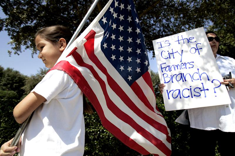 FILE - In this Aug. 26, 2006 file photo, Natalie Villafranca, 6, left, hold a flag as her mother, Elizabeth Villafranca, holds a sign in front of city hall in Farmers Branch, Texas, during an immigration law protest. The 5th U.S. Circuit Court of Appeals ruled Wednesday, March 21, 2012, that the ordinance passed by Farmers Branch in 2008 overstepped the town's authority, upholding a lower court ruling stopping a ban on illegal immigrants seeking housing. The law called on the city's building inspector to check the immigration status of anyone wanting to rent an apartment who wasn't a U.S. citizen. (AP Photo/L.M. Otero, File)