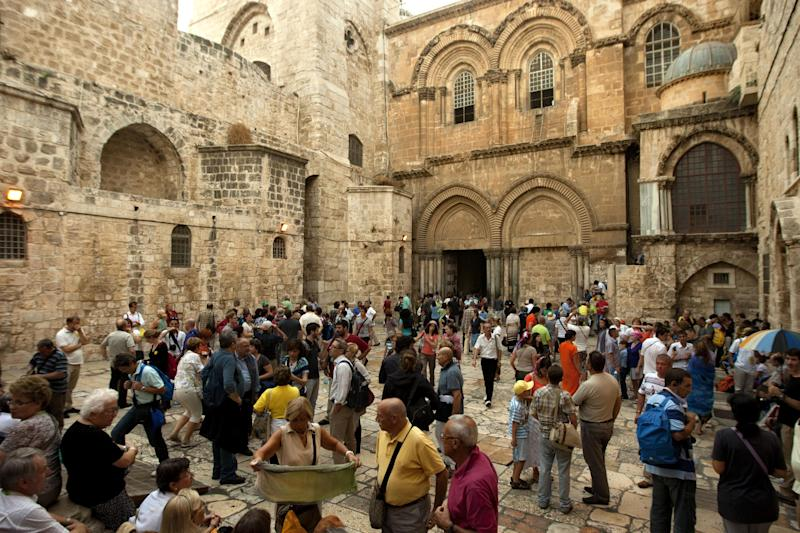 Tourists visit the Church of the Holy Sepulchre, in Jerusalem's Old City, Friday, Nov. 2, 2012. A clergyman from the church built on the site where Jesus Christ is said to have been crucified said Friday that its bank account has been frozen as the result of a long-standing dispute with an Israeli water company. (AP Photo/Sebastian Scheiner)