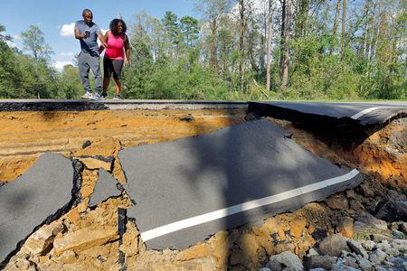 Passersby look at a section of washed-out road damaged by flood waters in the aftermath of Hurricane Florence, now downgraded to a tropical depression, in Currie, North Carolina, U.S., September 18, 2018. REUTERS/Jonathan Drake
