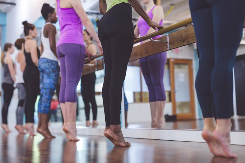 Multiethnic group of young women do barre & TRK suspension workout together at modern gym