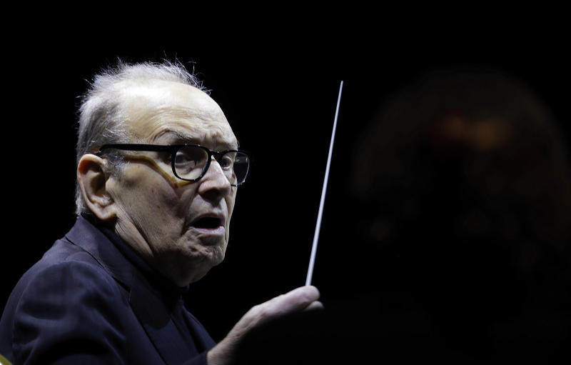 "Italian composer Ennio Morricone directs an ensemble during a concert of his ""60 Year Of Music World Tour"" in Milan, Italy, Tuesday, March 6, 2018. (AP Photo/Luca Bruno)"