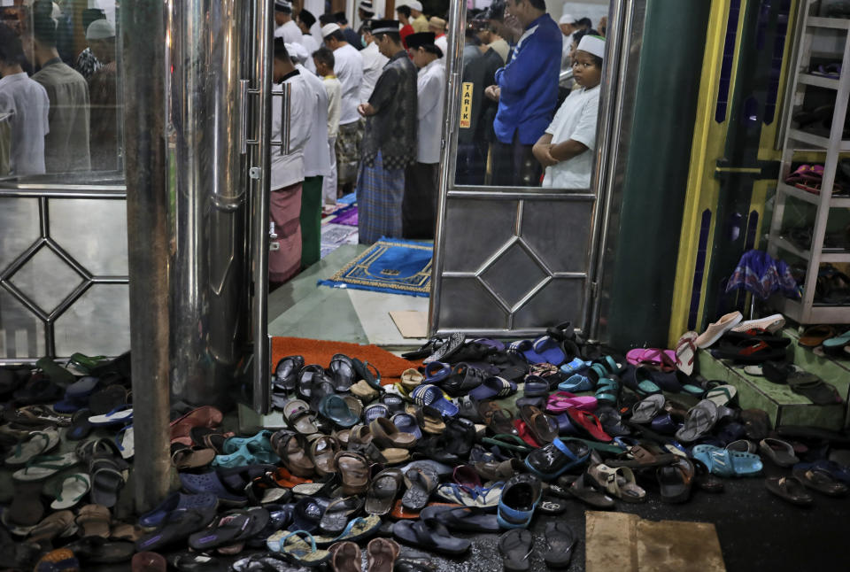 Footwear are left outside as people perform an evening prayer called 'tarawih' during the first evening of the holy fasting month of Ramadan, at a mosque in Jakarta, Indonesia, Monday, April 12, 2021. (AP Photo/Dita Alangkara)
