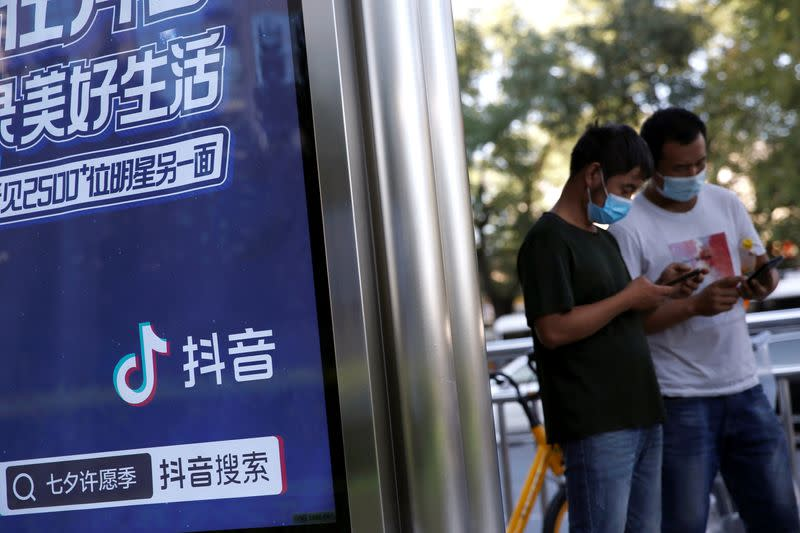FILE PHOTO: People wearing face masks use smartphones next to an advertisement of TikTok (Douyin) at a bus stop in Beijing