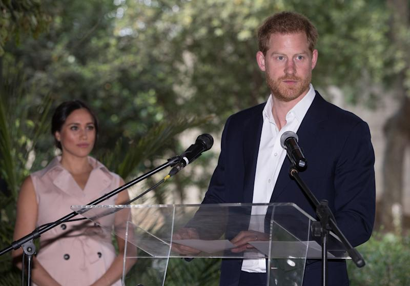Prince Harry addesses the press in Johannesburg South Africa while wife Meghan Markle watches on