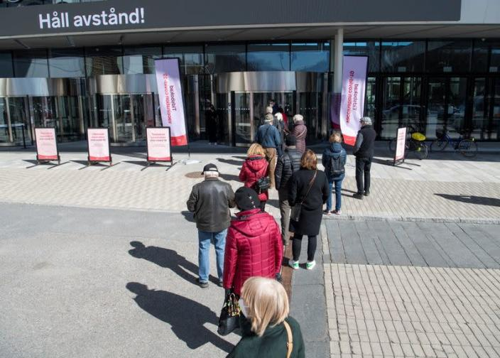 People stand in line to get a COVID-19 vaccine outside the Stockholmsmassan exhibition center, in Stockholm