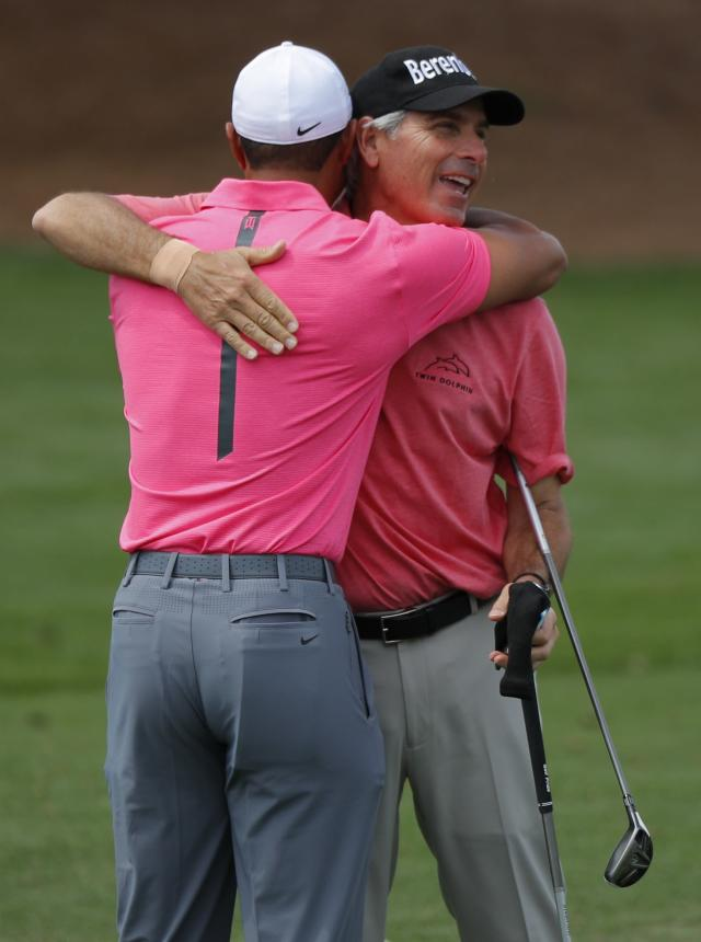 U.S. golfers Tiger Woods (L) and Fred Couples hug as they meet on the driving range during practice for the 2018 Masters golf tournament at Augusta National Golf Club in Augusta, Georgia, U.S. April 2, 2018. REUTERS/Brian Snyder
