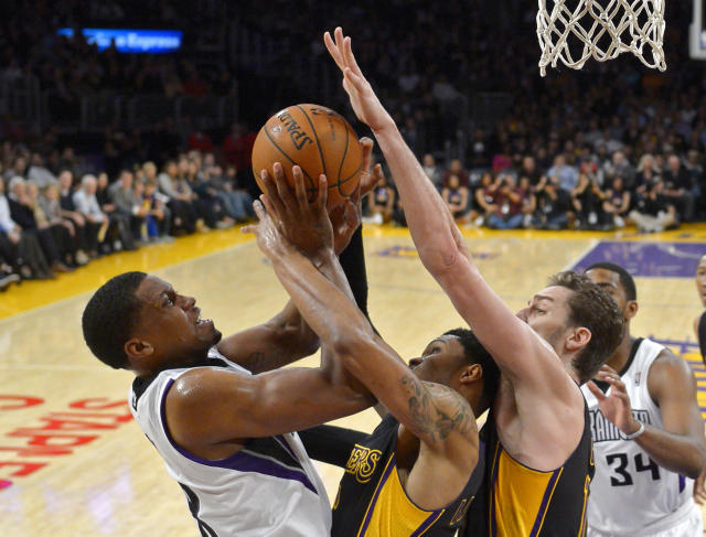 Sacramento Kings forward Rudy Gay, left, shoots as Los Angeles Lakers guard Kent Bazemore, center, and center Pau Gasol, of Spain, defend during the first half of an NBA basketball game on Friday, Feb. 28, 2014, in Los Angeles. (AP Photo/Mark J. Terrill)
