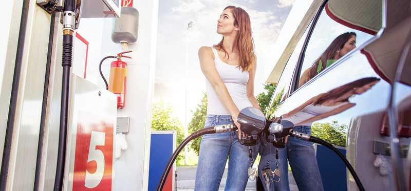 A woman pumping gas into her car at a gas station.