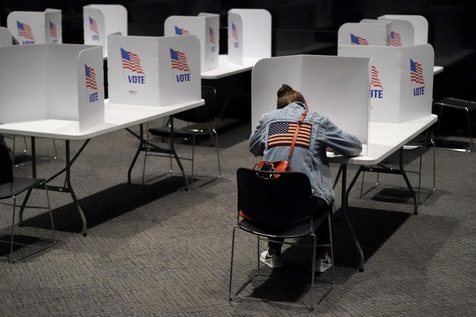 Laura Wooding votes at the National World War I museum on Election Day Tuesday, Nov. 3, 2020, in Kansas City, Mo. (AP Photo/Charlie Riedel)