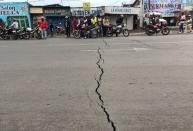 Congolese riders are seen near a crack on the road caused by earth tremors as aftershocks following the eruption of Mount Nyiragongo volcano near Goma