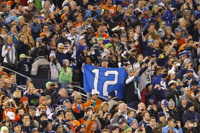 """Seattle Seahawks fans hold a """"12th Man"""" sign before the NFL Super Bowl XLVIII football game against the Denver Broncos Sunday, Feb. 2, 2014, in East Rutherford, N.J. (AP Photo/Paul Sancya)"""
