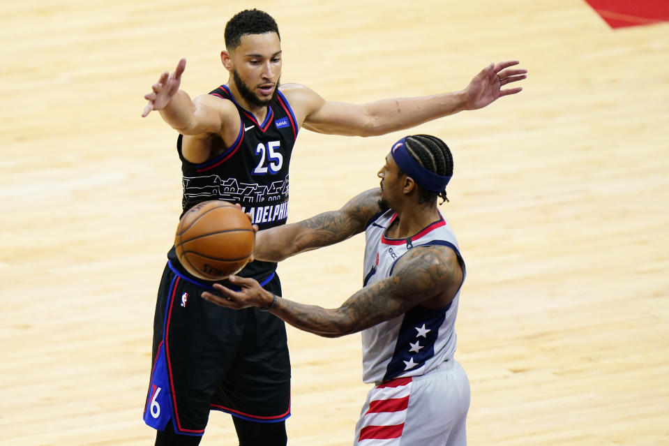 Philadelphia 76ers' Ben Simmons, top, tries to block a pass by Washington Wizards' Bradley Beal during the second half of Game 1 of a first-round NBA basketball playoff series, Sunday, May 23, 2021, in Philadelphia. (AP Photo/Matt Slocum)