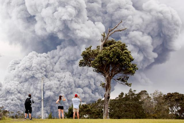 People watch as ash erupt from the Halemaumau crater near the community of Volcano during ongoing eruptions of the Kilauea Volcano in Hawaii, U.S., May 15, 2018. REUTERS/Terray Sylvester