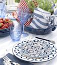 <p>No need to shop for a special table topper. Raid your cabinets for color-coordinated items instead. Here, crisp cotton napkins — cinched around a pair of potted plants with kitchen twine — and a tray transform into a fast, festive centerpiece. </p>