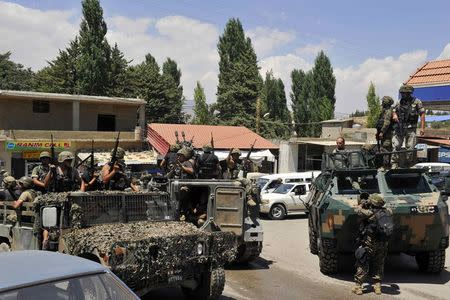 Lebanese army soldiers ride military vehicles, in Labwe in eastern Bekaa Valley