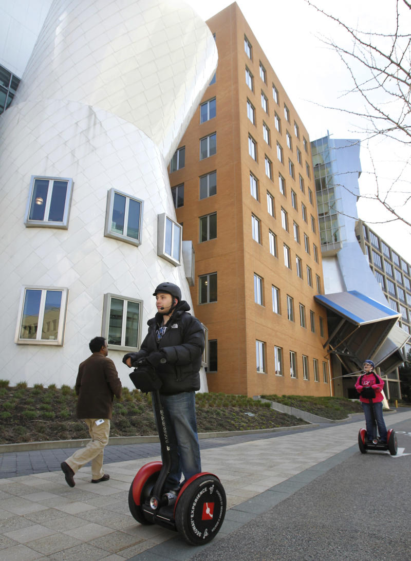 Waldo Holtzhausen, of Medfield, Mass., front, rides a two-wheel gyroscopic, personal transporter past Massachusetts Institute of Technology buildings during a Museum of Science tour, in Cambridge, Mass., Friday, April 15, 2011. The tour created by the Science Museum, featuring Segway transporters, visits shoreline areas along the Charles River, as well as various stops on and around the MIT campus.  (AP Photo/Steven Senne)