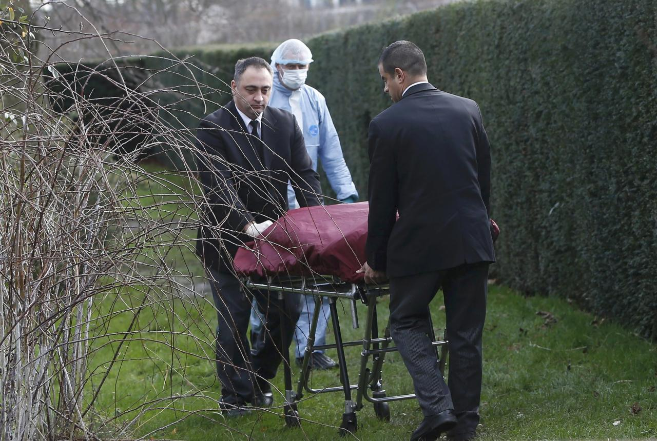 Undertakers remove a body from near the grounds of Kensington Palace in London, Britain