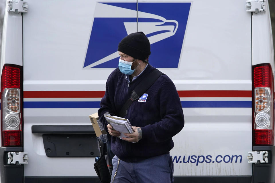 Postal carrier Josiah Morse heads out to deliver mail and packages, Wednesday, Feb. 3, 2021, in Portland, Maine. The U.S. Postal Service's stretch of challenges didn't end with the November general election and tens of millions of mail-in votes. The pandemic-depleted workforce fell further into a hole during the holiday rush, leading to long hours and a mountain of delayed mail. (AP Photo/Robert F. Bukaty)