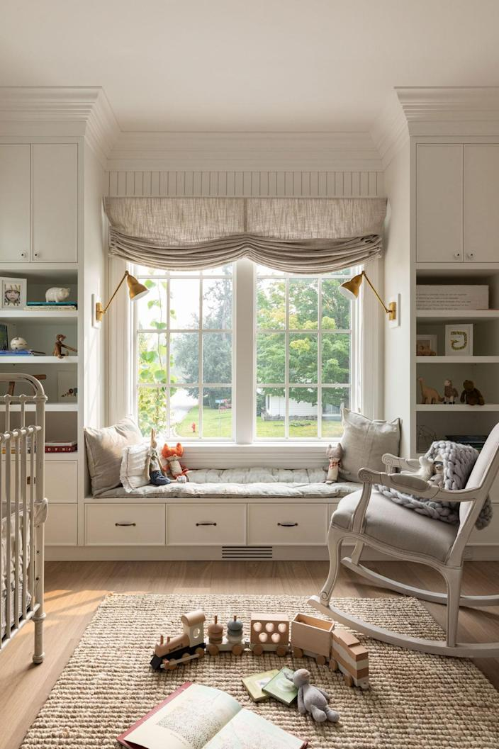 Ever with their children in mind, the Joneses used Sage Cabinetry and a vintage chair and crib for one of their children's rooms. A train by Magnolia Home and rug by Monika Hibbs Home knit the space together.